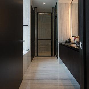 Idee per un'ampia stanza da bagno padronale moderna con ante lisce, ante nere, vasca sottopiano, doccia doppia, pavimento in marmo e top in marmo