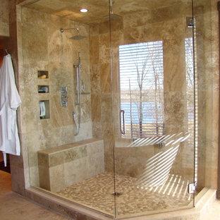 Imagen de cuarto de baño principal, minimalista, extra grande, con lavabo sobreencimera, ducha esquinera, baldosas y/o azulejos marrones, suelo de baldosas tipo guijarro, paredes beige y suelo de travertino