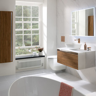Mediterranean family bathroom in West Midlands with flat-panel cabinets, medium wood cabinets, a freestanding bath, a wall mounted toilet, porcelain flooring, a vessel sink, solid surface worktops, grey floors and white worktops.