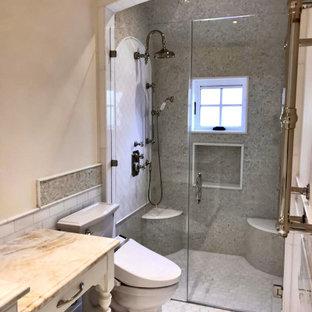 Idéer för att renovera ett mellanstort gul gult badrum med dusch, med möbel-liknande, gula skåp, en kantlös dusch, en toalettstol med separat cisternkåpa, vit kakel, marmorkakel, gula väggar, marmorgolv, ett undermonterad handfat, bänkskiva i onyx, vitt golv och dusch med gångjärnsdörr
