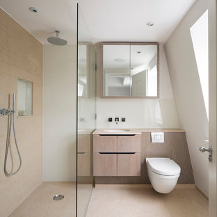 Inspiration for a modern shower room in London with flat-panel cabinets, light wood cabinets, an alcove shower, a wall mounted toilet, beige tiles, white walls, a submerged sink and an open shower.