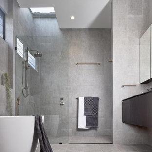 Modelo de cuarto de baño moderno con armarios con paneles lisos, puertas de armario grises, bañera exenta, ducha empotrada, baldosas y/o azulejos grises, suelo gris, ducha abierta y encimeras grises