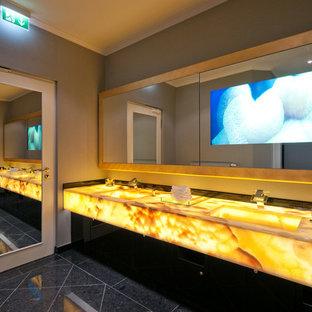 Foto di una grande stanza da bagno padronale contemporanea con nessun'anta, ante gialle, pareti beige, pavimento in pietra calcarea, lavabo integrato, top in onice, pavimento nero e top beige