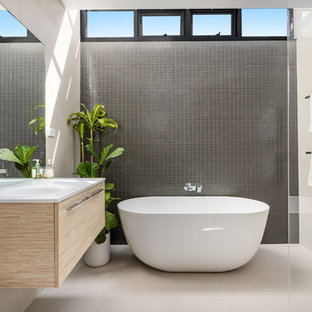 This is an example of a mid-sized contemporary master bathroom in Sydney with flat-panel cabinets, light wood cabinets, a freestanding tub, beige walls, a wall-mount sink, white benchtops, an open shower, porcelain tile, porcelain floors, beige floor and an open shower.