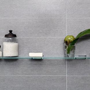 Bild på ett litet funkis en-suite badrum, med släta luckor, skåp i mörkt trä, ett fristående badkar, en toalettstol med hel cisternkåpa, flerfärgad kakel, glaskakel, grå väggar, klinkergolv i porslin, ett piedestal handfat och bänkskiva i glas