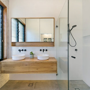 Inspiration for a large contemporary master bathroom in Sydney with ceramic floors, wood benchtops, an open shower, a double vanity, a floating vanity, flat-panel cabinets, medium wood cabinets, a curbless shower, white tile, a vessel sink, grey floor, brown benchtops and a niche.