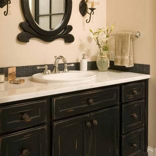 シアトルの小さいトラディショナルスタイルのおしゃれな浴室 (オーバーカウンターシンク、落し込みパネル扉のキャビネット、ヴィンテージ仕上げキャビネット、黒いタイル、モザイクタイル、ベージュの壁、磁器タイルの床) の写真
