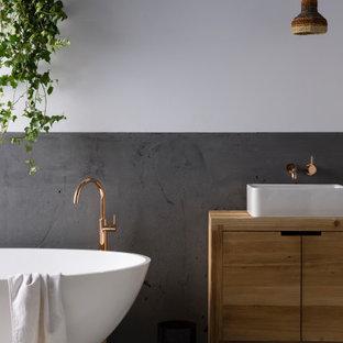 Großes Modernes Badezimmer En Suite mit braunen Schränken, freistehender Badewanne, grauen Fliesen, Zementfliesen, weißer Wandfarbe, Aufsatzwaschbecken, Waschtisch aus Holz, weißem Boden, brauner Waschtischplatte, Einzelwaschbecken und freistehendem Waschtisch in Auckland
