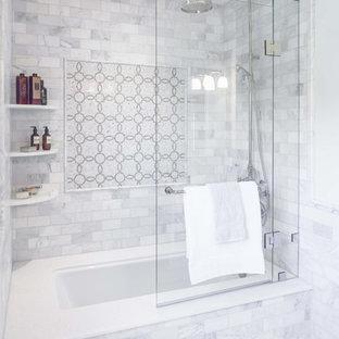 Foto på ett mellanstort vintage en-suite badrum, med luckor med upphöjd panel, grå skåp, en dusch/badkar-kombination, en toalettstol med hel cisternkåpa, grå kakel, vit kakel, porslinskakel, grå väggar, klinkergolv i porslin, ett undermonterad handfat, marmorbänkskiva, ett badkar i en alkov och grått golv