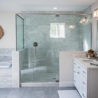Esempio di una stanza da bagno american style di medie dimensioni con lavabo da incasso, ante in stile shaker, ante bianche, top in marmo, vasca da incasso, pistrelle in bianco e nero, piastrelle di vetro, pareti grigie e pavimento in gres porcellanato