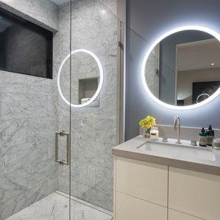 Immagine di un'ampia stanza da bagno minimal con ante lisce, ante beige, WC a due pezzi, piastrelle di marmo, pareti grigie, pavimento in marmo, lavabo sottopiano, top in cemento, porta doccia a battente e top beige