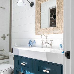 Foto de cuarto de baño infantil, exótico, de tamaño medio, con armarios estilo shaker, puertas de armario azules, bañera empotrada, ducha empotrada, baldosas y/o azulejos blancos, baldosas y/o azulejos de cemento, paredes blancas, lavabo integrado, ducha con puerta corredera y encimeras blancas