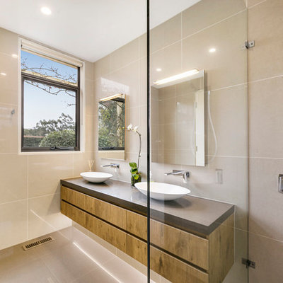 Bathroom - contemporary beige tile and porcelain tile porcelain tile and beige floor bathroom idea in Melbourne with furniture-like cabinets, medium tone wood cabinets, a wall-mount toilet, beige walls, a vessel sink, quartz countertops and brown countertops