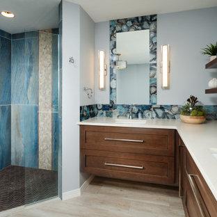 他の地域の中サイズのトランジショナルスタイルのおしゃれなマスターバスルーム (落し込みパネル扉のキャビネット、中間色木目調キャビネット、置き型浴槽、段差なし、分離型トイレ、青いタイル、ガラスタイル、グレーの壁、磁器タイルの床、アンダーカウンター洗面器、珪岩の洗面台、ベージュの床、開き戸のシャワー、ベージュのカウンター) の写真