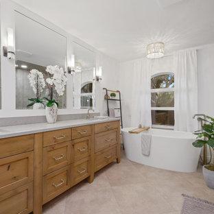 Aménagement d'une salle de bain classique avec un placard à porte shaker, des portes de placard en bois brun, une baignoire indépendante, un carrelage marron, un carrelage imitation parquet, un mur blanc, un lavabo encastré, un sol beige, un plan de toilette gris, meuble double vasque et meuble-lavabo sur pied.