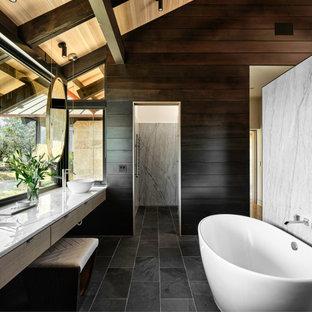 Mittelgroßes Modernes Badezimmer En Suite mit flächenbündigen Schrankfronten, hellen Holzschränken, freistehender Badewanne, grauen Fliesen, Marmorfliesen, brauner Wandfarbe, Schieferboden, Aufsatzwaschbecken, Quarzit-Waschtisch, schwarzem Boden, weißer Waschtischplatte, Doppelwaschbecken, schwebendem Waschtisch, Holzdecke, freigelegten Dachbalken, gewölbter Decke und Holzwänden in Austin