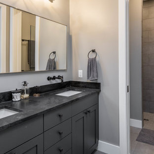 他の地域の中くらいのラスティックスタイルのおしゃれなマスターバスルーム (シェーカースタイル扉のキャビネット、茶色いキャビネット、アルコーブ型シャワー、分離型トイレ、ベージュのタイル、モザイクタイル、ベージュの壁、磁器タイルの床、ソープストーンの洗面台、ベージュの床、黒い洗面カウンター、アンダーカウンター洗面器) の写真