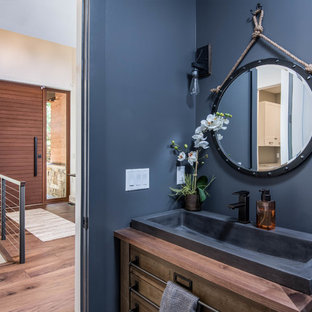 Inredning av ett rustikt litet brun brunt badrum med dusch, med släta luckor, bruna skåp, blå väggar, ljust trägolv, ett avlångt handfat, träbänkskiva och beiget golv