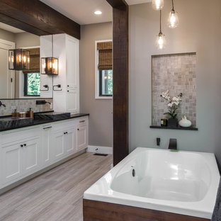 Example of a mid-sized mountain style master beige tile and mosaic tile porcelain floor and beige floor bathroom design in Other with shaker cabinets, white cabinets, a two-piece toilet, beige walls, a trough sink, soapstone countertops and black countertops