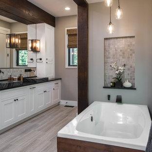 На фото: главная ванная комната среднего размера в стиле рустика с фасадами в стиле шейкер, белыми фасадами, отдельно стоящей ванной, душем в нише, раздельным унитазом, бежевой плиткой, плиткой мозаикой, бежевыми стенами, полом из керамогранита, раковиной с несколькими смесителями, столешницей из талькохлорита, бежевым полом и черной столешницей
