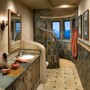 Идея дизайна: главная ванная комната в стиле фьюжн с врезной раковиной, столешницей из плитки, душем без бортиков, темными деревянными фасадами, коричневой плиткой, серой плиткой, фасадами с утопленной филенкой, плиткой из сланца, бежевыми стенами, полом из травертина, бежевым полом и открытым душем