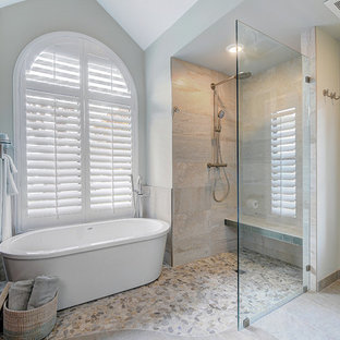 Bild på ett stort maritimt en-suite badrum, med ett undermonterad handfat, släta luckor, skåp i mörkt trä, granitbänkskiva, ett fristående badkar, en kantlös dusch, en toalettstol med separat cisternkåpa, grå kakel, porslinskakel, vita väggar och klinkergolv i småsten