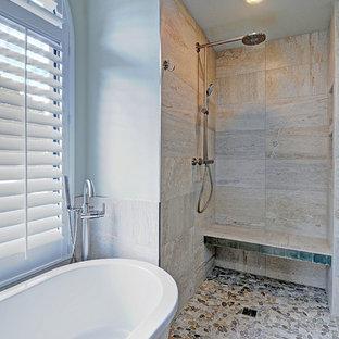 Modelo de cuarto de baño principal, marinero, grande, con lavabo bajoencimera, armarios con paneles lisos, puertas de armario de madera en tonos medios, encimera de granito, bañera exenta, ducha a ras de suelo, sanitario de dos piezas, baldosas y/o azulejos grises, baldosas y/o azulejos de porcelana, paredes blancas y suelo de baldosas tipo guijarro