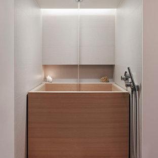 Idee per una stanza da bagno padronale etnica di medie dimensioni con lavabo sottopiano, ante lisce, top in vetro, vasca giapponese, WC monopezzo, piastrelle beige, piastrelle in gres porcellanato, pareti bianche, pavimento in gres porcellanato, ante grigie e doccia aperta