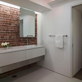 Ispirazione per una stanza da bagno padronale industriale di medie dimensioni con lavabo sottopiano, ante lisce, top in vetro, vasca giapponese, piastrelle in gres porcellanato, pareti bianche, pavimento in gres porcellanato, ante grigie, doccia aperta, WC sospeso e piastrelle nere