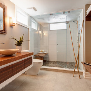 Diseño de cuarto de baño asiático con lavabo sobreencimera, encimera de madera y encimeras marrones