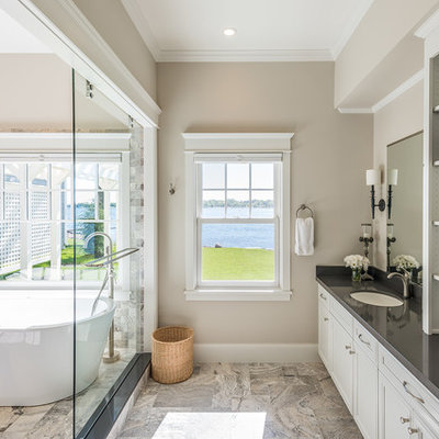 Large elegant master multicolored tile and stone tile porcelain tile bathroom photo in Minneapolis with flat-panel cabinets, white cabinets, an undermount sink, beige walls, solid surface countertops and gray countertops