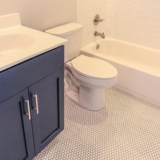 Diseño de cuarto de baño infantil, costero, de tamaño medio, con armarios estilo shaker, puertas de armario azules, bañera empotrada, sanitario de una pieza, baldosas y/o azulejos blancos, paredes grises, suelo con mosaicos de baldosas, encimera de cuarzo compacto y suelo blanco