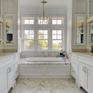 Esempio di una stanza da bagno padronale tradizionale di medie dimensioni con ante con riquadro incassato, ante bianche, vasca da incasso, piastrelle in gres porcellanato, pareti blu, pavimento in marmo, lavabo sottopiano, top in quarzo composito, piastrelle beige, pavimento beige e top beige