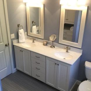 Immagine di una piccola stanza da bagno padronale country con ante a filo, ante bianche, WC a due pezzi, pareti blu, pavimento in gres porcellanato, lavabo integrato, top in onice e pavimento grigio