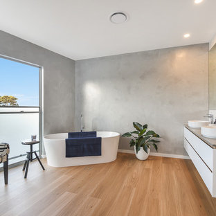 This is an example of a contemporary bathroom in Sunshine Coast with flat-panel cabinets, white cabinets, a freestanding tub, grey walls, medium hardwood floors, a vessel sink, brown floor and grey benchtops.