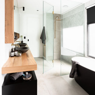 Photo of an industrial bathroom in Melbourne with black cabinets, a freestanding tub, gray tile, white walls, a vessel sink, wood benchtops, grey floor, brown benchtops, a double vanity and a floating vanity.