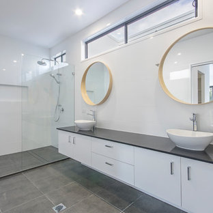 This is an example of a large contemporary master bathroom in Sunshine Coast with white cabinets, an open shower, a one-piece toilet, white tile, porcelain tile, white walls, porcelain floors, a vessel sink, engineered quartz benchtops, grey floor, an open shower and black benchtops.