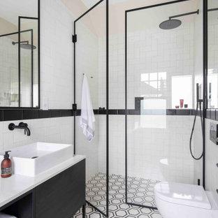 На фото: главные ванные комнаты среднего размера в стиле лофт с плоскими фасадами, черными фасадами, открытым душем, белой плиткой, плиткой кабанчик, столешницей из гранита, душем с распашными дверями и белой столешницей