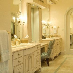 Idee per una grande stanza da bagno padronale chic con ante con bugna sagomata, ante bianche, vasca ad alcova, piastrelle blu, piastrelle a mosaico, pareti beige, pavimento in pietra calcarea, lavabo sottopiano, top in onice e pavimento beige