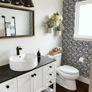 Cette photo montre une petit salle d'eau nature avec un placard à porte affleurante, des portes de placard blanches, un mur multicolore, un sol en bois foncé, un plan de toilette noir, des toilettes cachées, meuble simple vasque, meuble-lavabo sur pied et du papier peint.