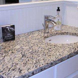 Esempio di una stanza da bagno padronale con lavabo sottopiano, ante con bugna sagomata, ante bianche, top in marmo, vasca sottopiano e pareti bianche