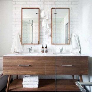 Foto på ett stort 50 tals en-suite badrum, med vit kakel, vita väggar, klinkergolv i keramik, ett undermonterad handfat, bänkskiva i akrylsten, släta luckor, skåp i mörkt trä, en toalettstol med separat cisternkåpa, tunnelbanekakel och grått golv