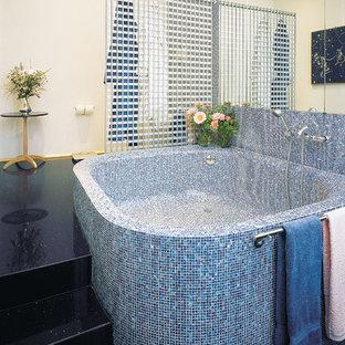 Foto de cuarto de baño principal, actual, grande, con bañera exenta, paredes beige, suelo de terrazo y suelo negro