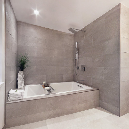 ... cabinets, white cabinets, engineered quartz countertops, a drop-in tub