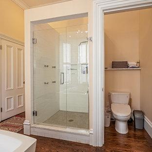Immagine di una stanza da bagno padronale chic di medie dimensioni con ante rosse, vasca freestanding, doccia alcova, WC a due pezzi, pareti beige, parquet scuro, lavabo sottopiano, top in marmo, pavimento beige e porta doccia a battente