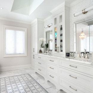 Imagen de cuarto de baño principal, tradicional renovado, de tamaño medio, con armarios con paneles empotrados, puertas de armario blancas, baldosas y/o azulejos blancos, baldosas y/o azulejos en mosaico, paredes grises, lavabo bajoencimera, suelo de mármol y encimera de mármol