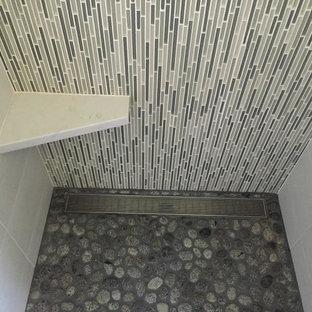 Diseño de cuarto de baño principal, moderno, de tamaño medio, con armarios con paneles lisos, puertas de armario de madera en tonos medios, bañera esquinera, ducha abierta, baldosas y/o azulejos de cemento, paredes blancas, lavabo de seno grande y encimera de cuarcita