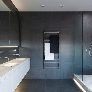 Imagen de cuarto de baño principal, minimalista, grande, con armarios con paneles lisos, puertas de armario blancas, ducha esquinera, paredes grises, lavabo integrado, encimera de cuarzo compacto, suelo de baldosas de porcelana y suelo gris