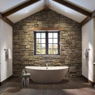 Ejemplo de cuarto de baño principal, rural, grande, con armarios tipo mueble, puertas de armario de madera en tonos medios, bañera exenta, baldosas y/o azulejos de piedra, paredes blancas, suelo de madera oscura, lavabo bajoencimera y encimera de acrílico