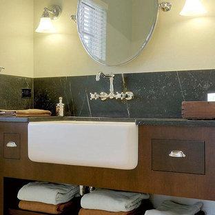 Diseño de cuarto de baño con ducha, clásico renovado, de tamaño medio, con armarios con paneles lisos, puertas de armario de madera en tonos medios, baldosas y/o azulejos negros, paredes beige, suelo con mosaicos de baldosas, lavabo bajoencimera, encimera de esteatita y suelo blanco